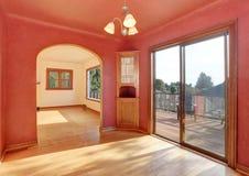 Intérieur de couloir dans des tons rouges avec le plancher en bois dur La salle a la sortie au balcon Photographie stock