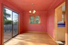 Intérieur de couloir dans des tons rouges avec le plancher en bois dur La salle a la sortie au balcon Image libre de droits