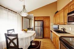 Intérieur de cuisine confortable et de salle à manger avec l'ensemble noir de table et les coffrets bruns image stock