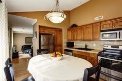 Intérieur de cuisine confortable et de salle à manger avec l'ensemble noir de table et les coffrets bruns photo stock