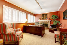 Intérieur de Home Office avec les murs et la cheminée rouges. Photos libres de droits