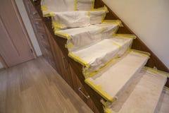 Intérieur de maison avec l'escalier en bois de chêne couvert de couverture protectrice de tissu pendant les travaux de rénovation Image stock