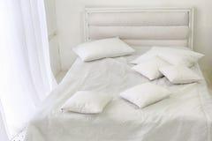 Intérieur de pièce blanche avec le lit, fenêtre, oreillers photo stock