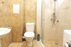 Intérieur de salle de bains d'hôtel avec la cabine et la machine à laver de douche image libre de droits