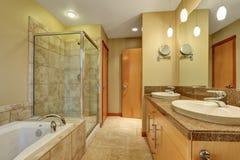 Intérieur de salle de bains dans des tons beiges avec le coffret de vanité avec le plan de travail de granit images stock