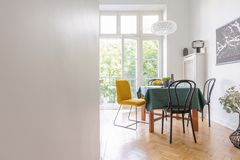 Intérieur de salon avec la nappe et genre différent de chaises, carte noire sur le mur, vraie photo avec image libre de droits