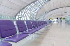 Intérieur de terminal d'aéroport avec des rangées des sièges vides Image stock