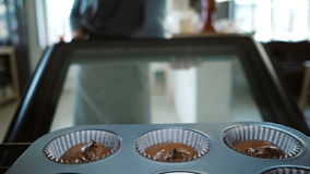 Intérieur de vue : four ouvert de jeune femme et mise dans le plateau de cuisson pour des petits gâteaux Danse femelle tout en at