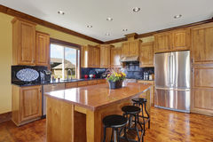 Intérieur en bois de cuisine avec une île et des appareils d'acier Photos stock
