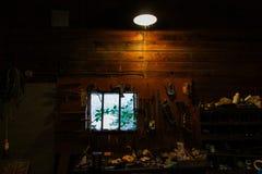 Intérieur foncé d'un établi en bois malpropre avec toutes sortes d'outils jetés autour photographie stock