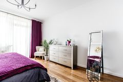Intérieur gentil de chambre à coucher avec le fauteuil, le support de TV et le miroir comme décorations images libres de droits