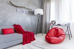 Intérieur gris avec la chaise rouge de sac Photos stock