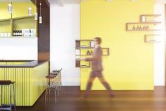 Intérieur jaune de bar, étagères sur le mur, homme d'affaires Photos stock