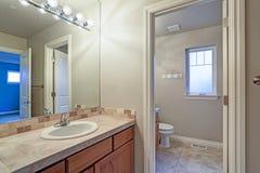 Intérieur léger de salle de bains avec le coffret supérieur carrelé de vanité photographie stock