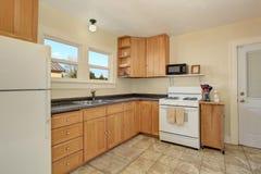 Intérieur lumineux de pièce de cuisine avec les coffrets de couleur de miel et le plancher de tuiles Image libre de droits
