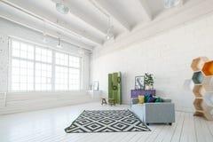 Intérieur lumineux de studio ou de salon de photo avec la grande fenêtre, plancher en bois à haut plafond et blanc, sofa moderne  Photos libres de droits
