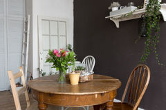 Intérieur meublé avec la chaise, table avec des fleurs images stock