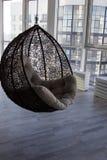 Intérieur moderne avec la canne-chaise de suspension et les fenêtres panoramiques Image stock