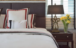 Intérieur moderne de chambre à coucher avec les oreillers et la lampe de lecture sur la table Photos libres de droits