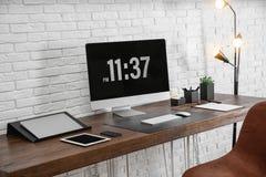 Intérieur moderne de lieu de travail avec l'ordinateur et les dispositifs sur la table photos stock