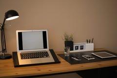 Intérieur moderne de lieu de travail avec l'ordinateur portable et les dispositifs sur la table photos libres de droits