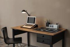 Intérieur moderne de lieu de travail avec l'ordinateur portable et les dispositifs sur la table photographie stock libre de droits