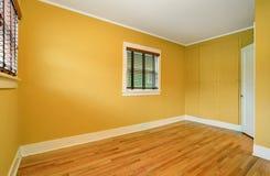 Intérieur vide de pièce dans les tons jaunes et le plancher en bois dur Image libre de droits