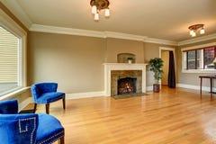 Intérieur vide de salon avec la cheminée et les fauteuils bleus Photos stock