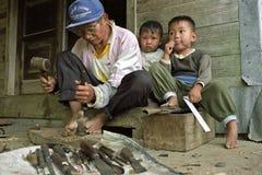 Intagliatore del legno filippino sul lavoro con i suoi bambini Immagini Stock
