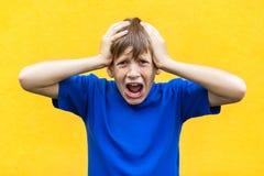 Inte! Huvud och skri för ung pojke rörande Inomhus skjutit Arkivbild