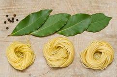 Inte lagad mat pasta och kryddor som ligger på det gamla brädet Arkivfoto