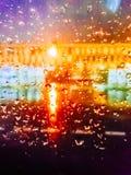 Inte skarpt vatten tappar på exponeringsglas med färgade ljus Royaltyfri Fotografi