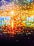 Inte skarpt vatten tappar på exponeringsglas med färgade ljus Arkivfoto