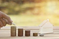 Inteckna begreppet, hand staplade pengar på mynt med det wood huset på den wood tabellen, begrepp som köpande, besparingen som sä royaltyfria foton
