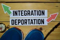 Integracja lub deportacja naprzeciw kierunków znaków z sneakers, eyeglasses i kompasem na drewnianym, zdjęcie stock