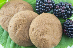 Integral biscuits and fresh blackberries on blackberry leaves Stock Photo