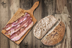 Bacon Rashers On Cutting Board And Dark Integral Wholegrain Bread Cut Loaf Set On Old Weathered Coarse Wood Grunge Background royalty free stock photos