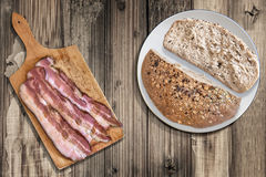 Integral Bread and Cutting Board with Bacon Rashers on Wood Stock Photos