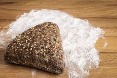 Integral bread in the form of a triangle with linseed, oats and sesame seeds. Triangle-shaped wholemeal bread with linseed, oats and sesame seeds next to some royalty free stock photos
