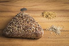 Integral bread in the form of a triangle with linseed, oats and sesame seeds. Triangle-shaped wholemeal bread with linseed, oats and sesame seeds next to some royalty free stock images