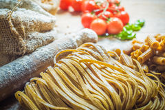 Integral components of tagliatelle pasta ingredients and tomatoe Stock Image
