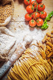 Integral components of tagliatelle pasta ingredients and tomatoe Royalty Free Stock Images