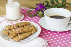 Integral cookies for breakfast. Oatmeal and linen integral cookies on white and pink polka dots tablecloth, prepared with a cup of coffee and some milk, ready Royalty Free Stock Images
