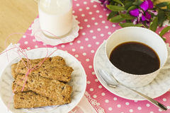 Integral cookies for breakfast. Oatmeal and linen integral cookies on white and pink polka dots tablecloth, prepared with a cup of coffee and some milk, ready Royalty Free Stock Image