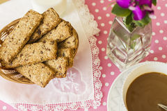 Integral cookies for breakfast. Oatmeal and linen integral cookies on white and pink polka dots tablecloth, prepared with a cup of coffee and some milk, ready Royalty Free Stock Photos