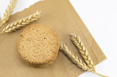 Integral cookies and wheat plant on the cooking paper. Integral cookies and yellow wheat plant on a brown cooking paper Royalty Free Stock Photography
