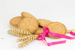 Integral cookies and wheat plant on white baclground. Integral cookies and a decprated wheat plant on white baclground Royalty Free Stock Photography