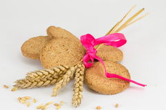 Integral cookies and wheat plant on white baclground. Integral cookies and a decprated wheat plant on white baclground Royalty Free Stock Photo