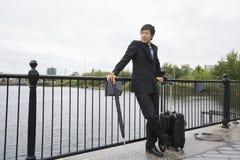 Integral de hombre de negocios con el equipaje que se inclina en la verja a lo largo del río fotografía de archivo libre de regalías