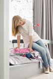 Integral de la muchacha que intenta cerrar la maleta en casa Imagenes de archivo